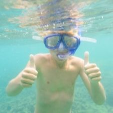 kid snorkeling and giving two thumbs up