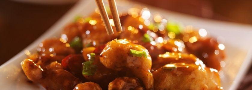 chopsticks grabbing a piece of orange glaze chicken