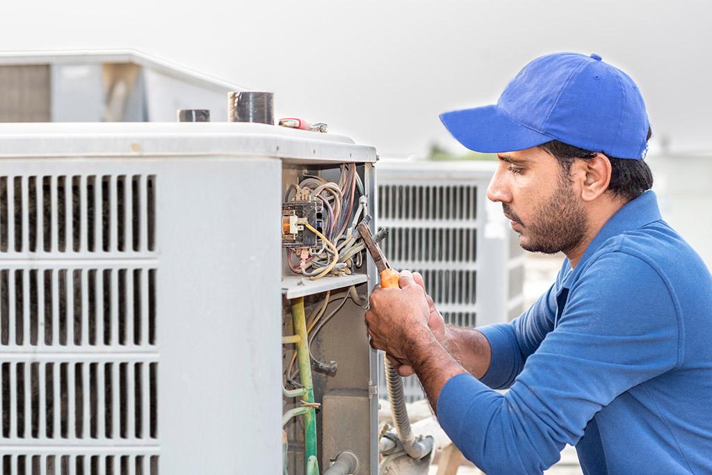 man repairing outdoor air conditioning unit