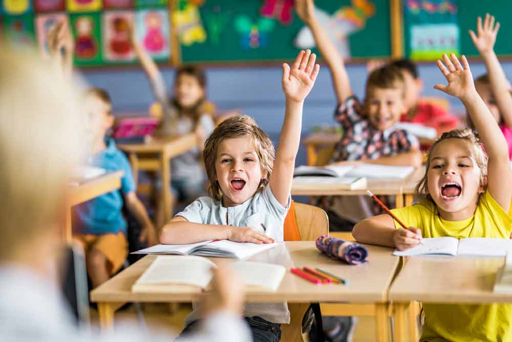 smiling kids raising hands in kindergarten classroom