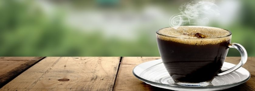 steaming black coffee on outdoor wood table