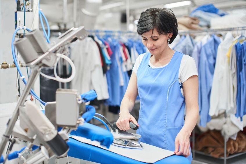 woman ironing garment in dry cleaners