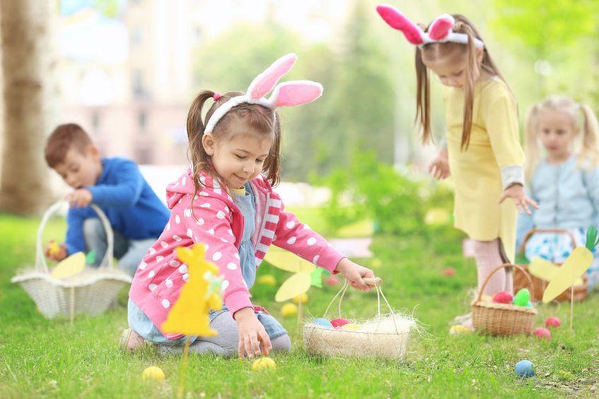 toddlers smiling on an outdoor easter egg hunt