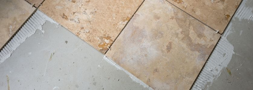 new travertine tile being laid