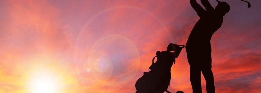 golfer driving ball into sunset