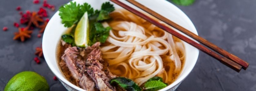 pho with cilantro and lime wedges