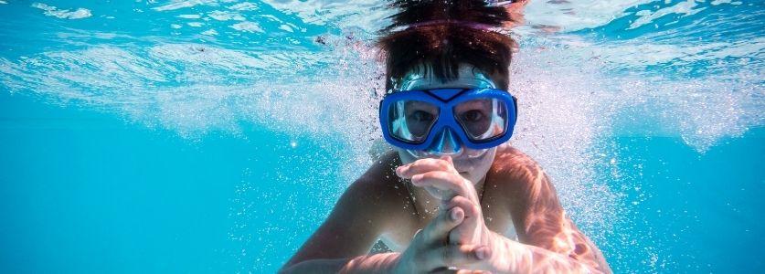 kids swimming underwater in pool