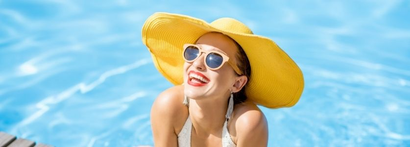 woman in yellow hat smiling at pool side