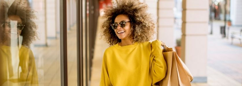 olive skinned woman smiling while shopping