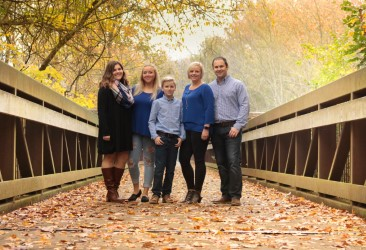 A photo of Karen Garner surrounded by her family on an uncovered wooden bridge during autumn.