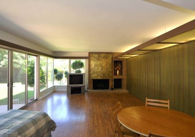 Silver lake mid century home has a family room with fireplace and opens to a flat backyard