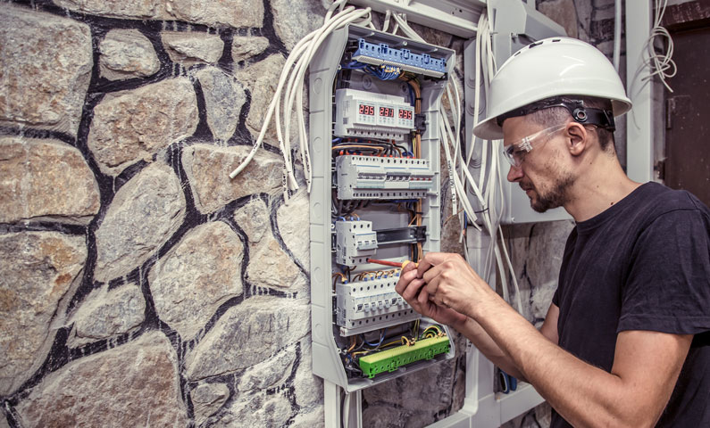 Male electrician works in a switchboard with an electrical connecting cab