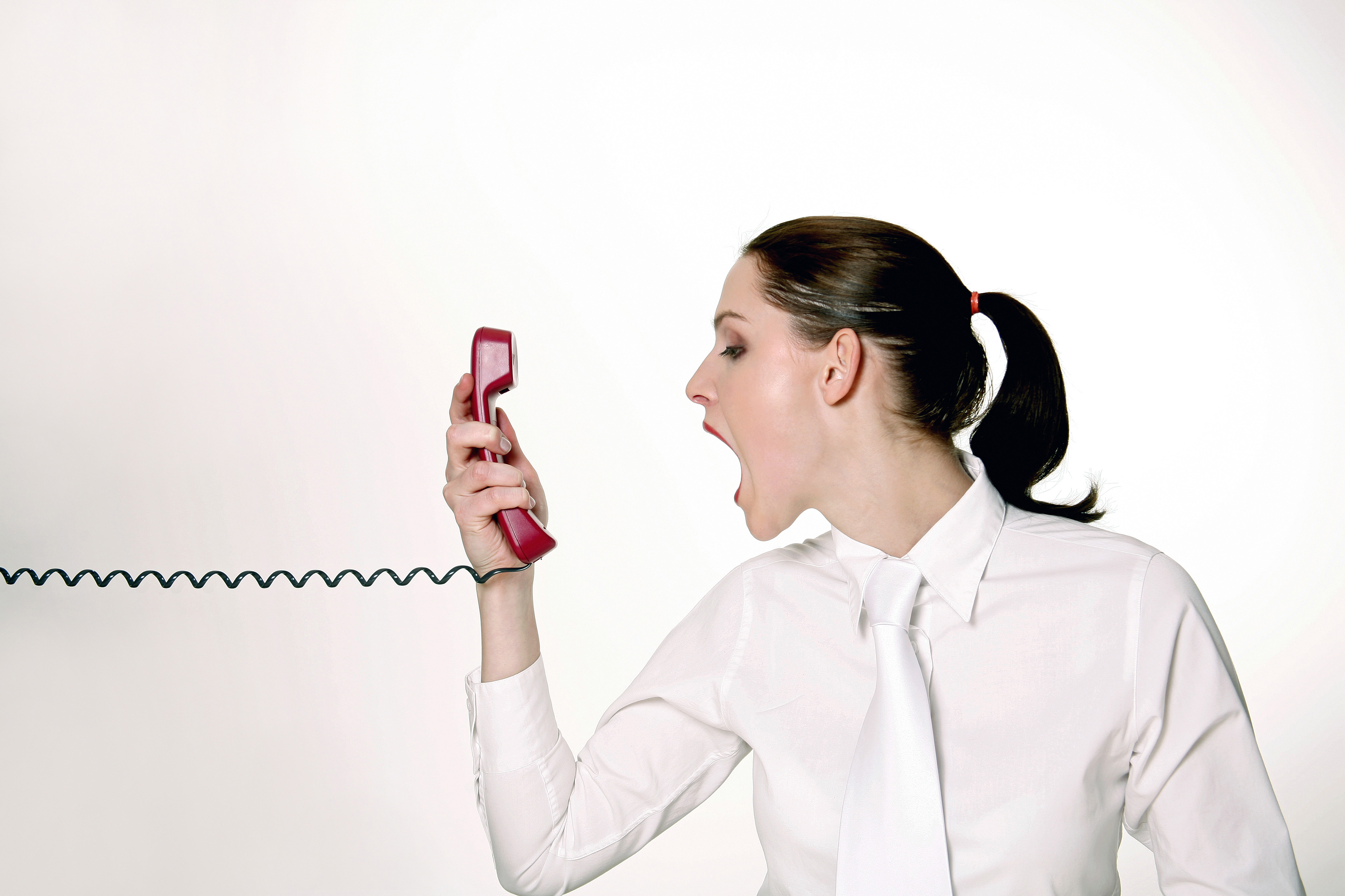 angry woman yelling at phone over high interest rate