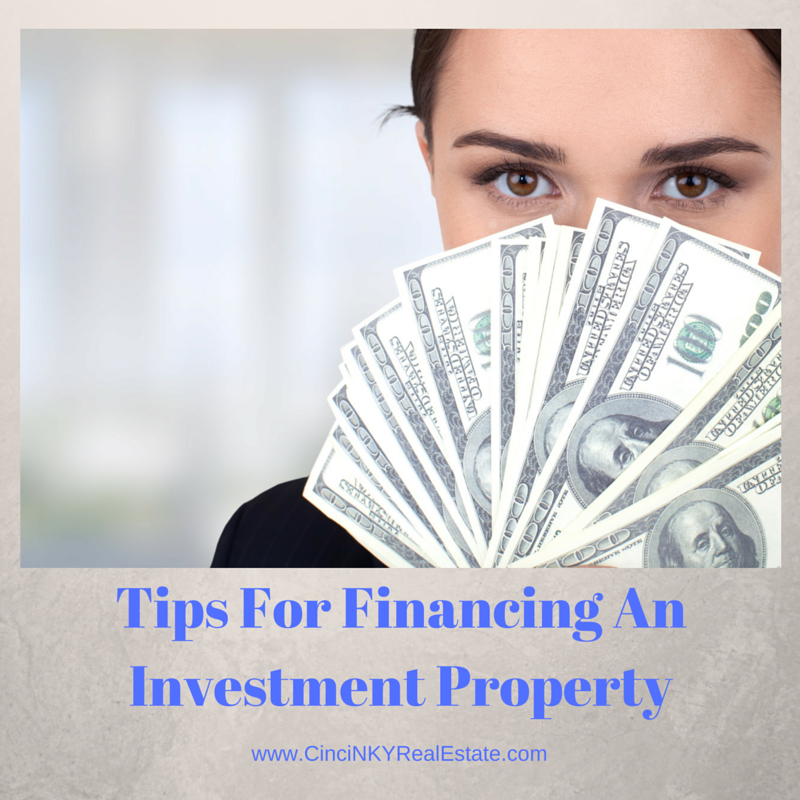 picture of woman holding money for tips for financing an investment property