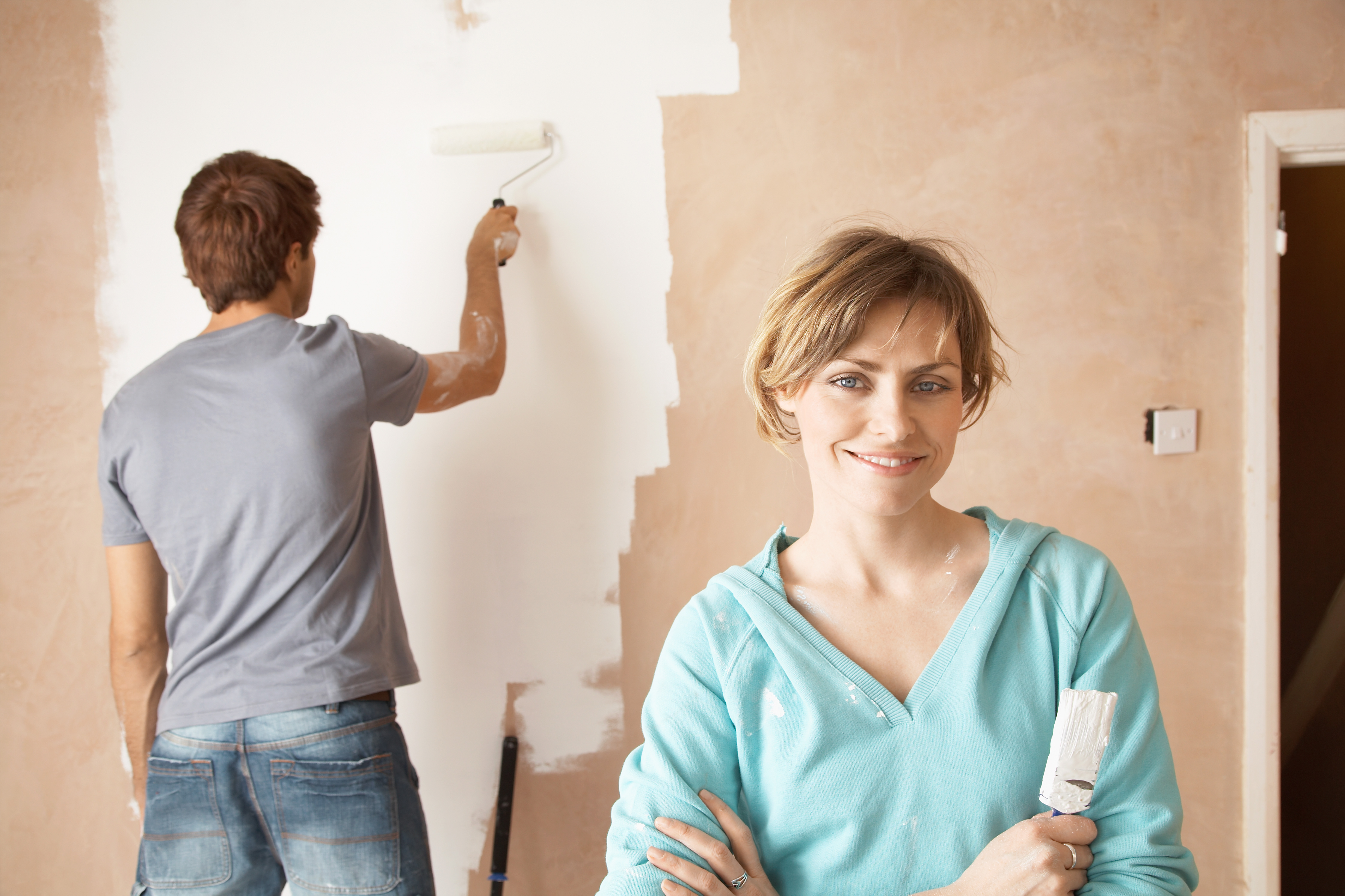 couple painting their own house to get it ready for sale