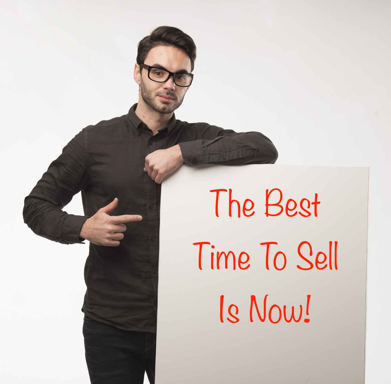 man with sign that says the best time to sell is now