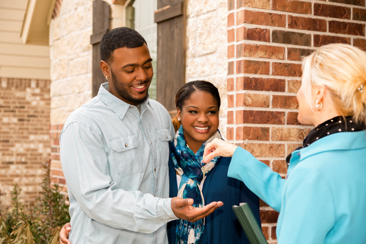 young couple receiving keys to a house they bought