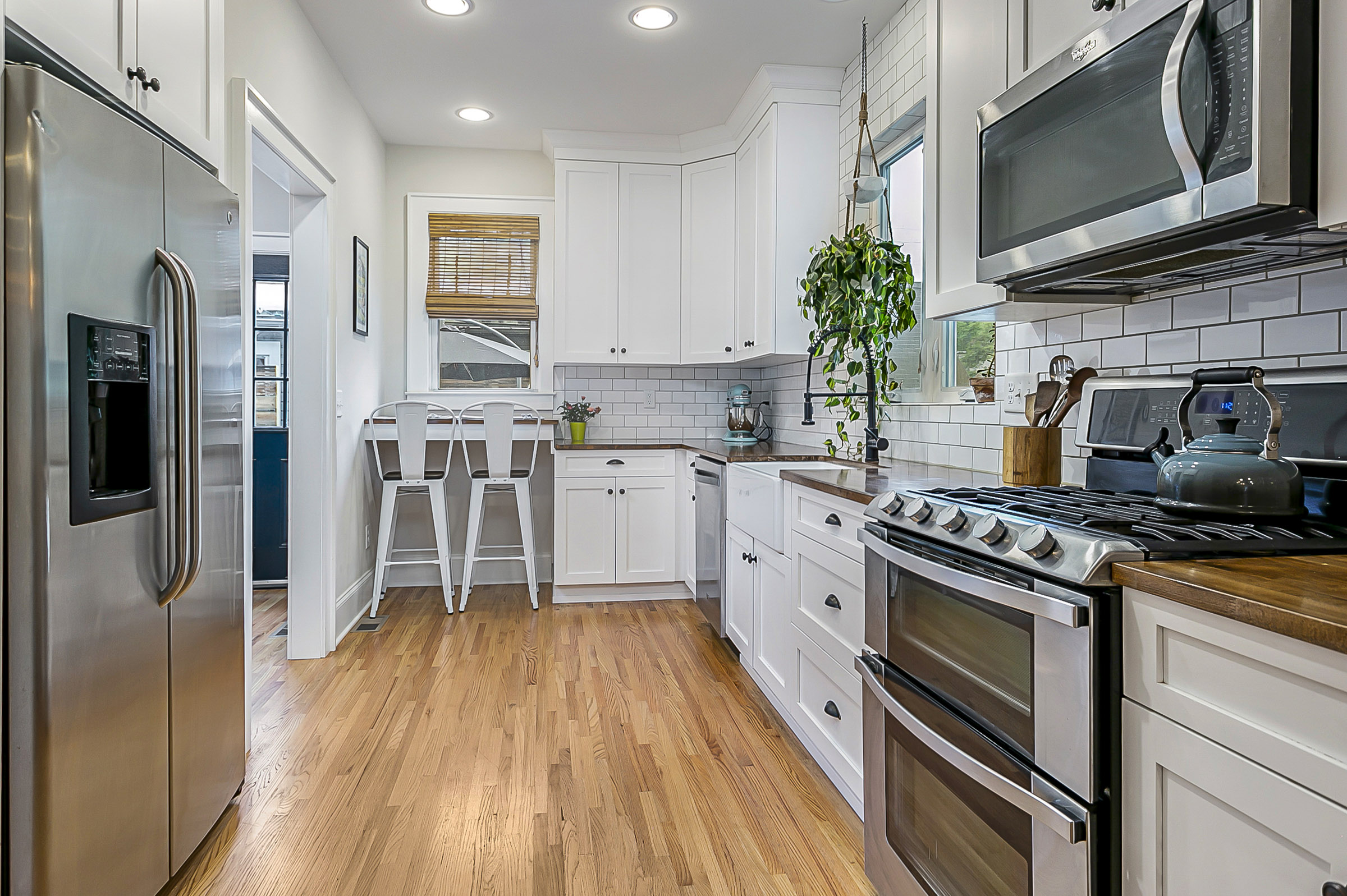 Gallery style kitchen with white cabinets and stainless steel appliances