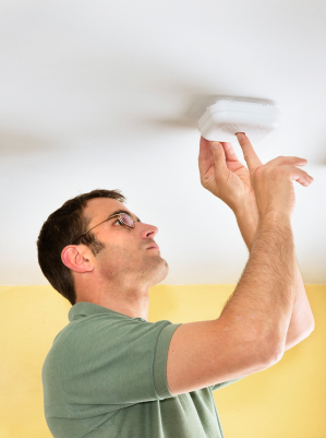 Man checking carbon monoxide detector.