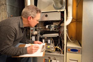 Professional inspecting HVAC system