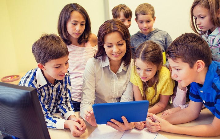 Kids with teacher gathered around tablet