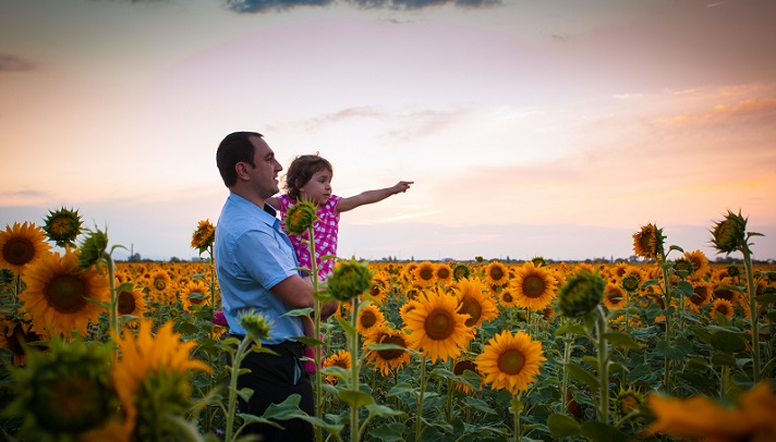 Father and daughter in sunflower field