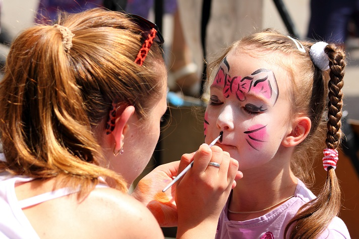 Little girl at festival having her face painted by artist