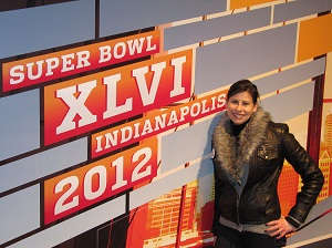 Kristie Smith poses next to Super Bowl 2012 sign in Indianapolis.