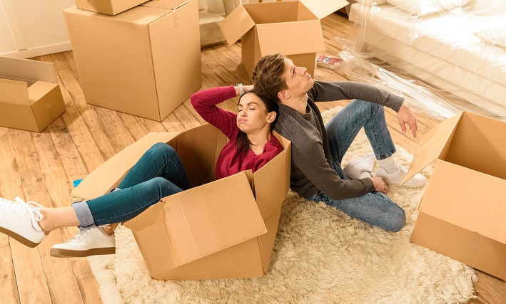 exhausted couple with moving boxes