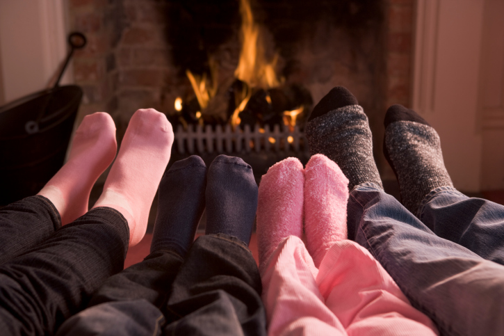 Family's feet warming before a fire in a fireplace
