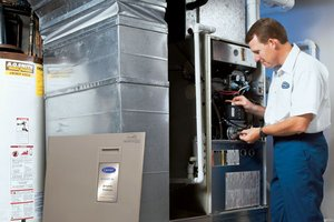 Professional checks furnace for maintenance issues.