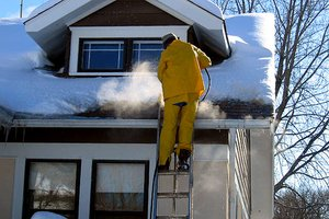 Maintenance professional removing ice dams from roof.