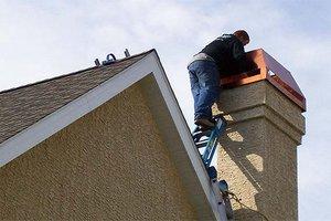 Man inspecting chimney for damage.