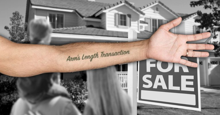 A person's arm with an arm's length transaction tattoo in front of a house for sale.