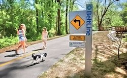 A family walking their dog along an Atlanta Beltline walking path.
