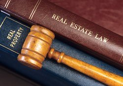 Two real estate law books in an attorney's office with a gavel on top of them.
