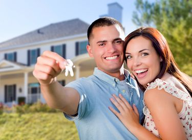 A happy young couple in front of the home they just purchased.