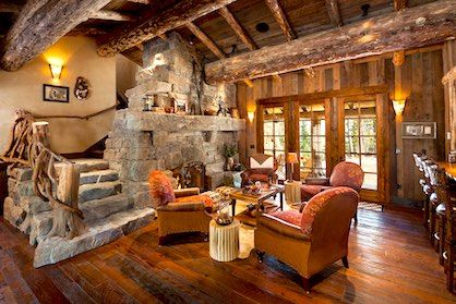 Living room with exposed wood beams & stone fireplace in a luxury cabin style home.