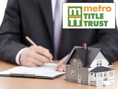 A closing attorney signing documents with Metro Title Trust logo.