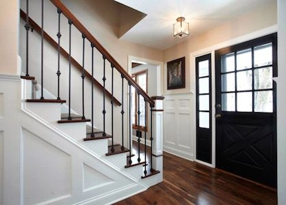 Front door and entry foyer with hardwood floors in an updated center hall colonial.