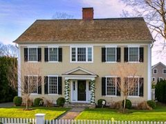 Stately two story center hall colonial home on half acre lot with white picket fence.