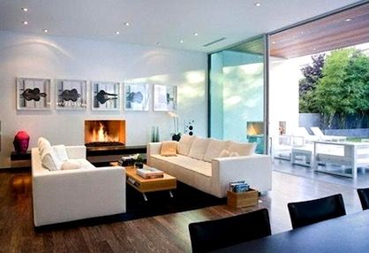 Sleek, contemporary living room with fireplace opens to a covered outdoor sitting area.