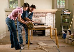 A husband and wife cutting wood for their home renovation project.