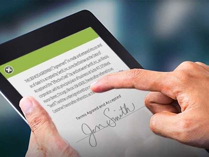 Man signing document on iPad using eSign signature platform.