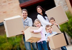 A family of five each carrying a moving box after successfully selling their home by owner.