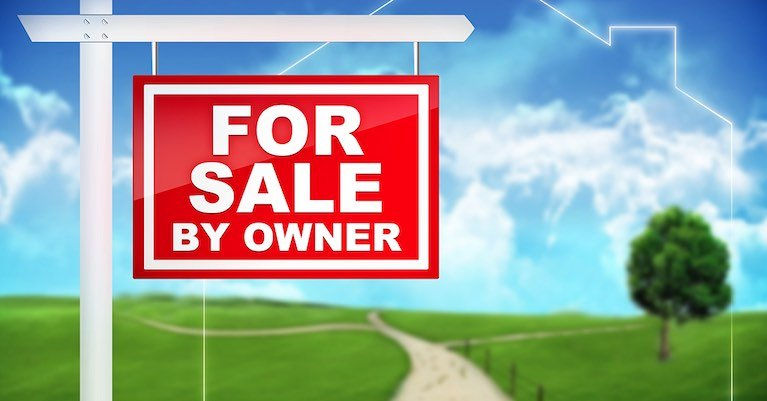 A for sale by owner yard sign with sky background.