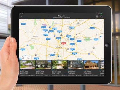 A person viewing real estate listings for sale on an iPad using the GoFMLS app.