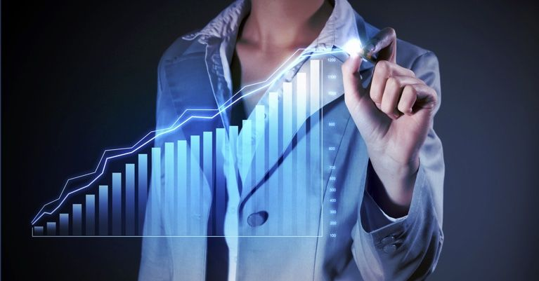 Woman in front of graph of housing market trends.