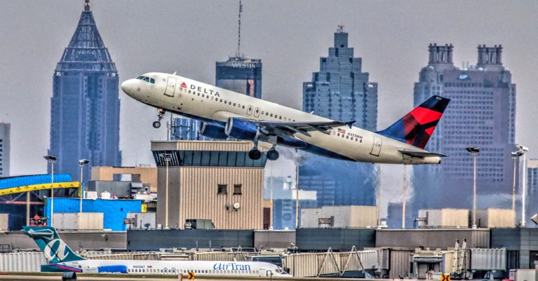 A Delta flight leaving the runway of Hartsfield-Jackson with Atlanta skyline in the background.