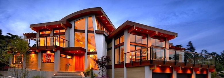 Large modern style home with walls of windows.
